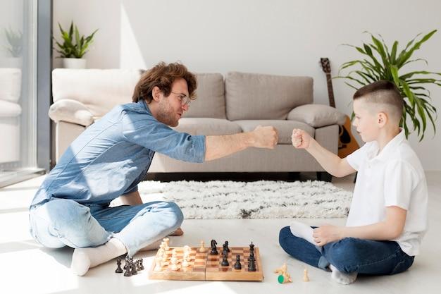 Tutor und junge spielen schach auf dem boden