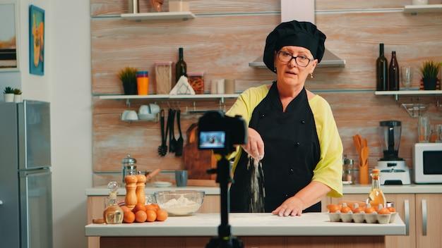 Tutorial über mehl während der aufnahme der lebensmittelzubereitung in der heimischen küche. pensionierter blogger-koch-influencer, der internet-technologie verwendet, kommuniziert und blogging in sozialen medien mit digitaler ausrüstung fotografiert