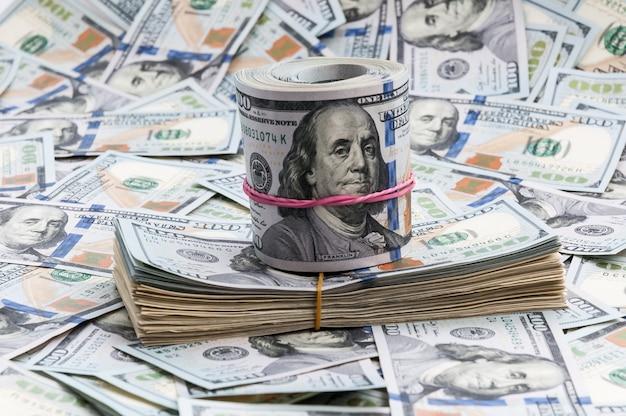 Tutu und rolle von dollar auf einem hintergrund von rechnungen von hundert dollar.