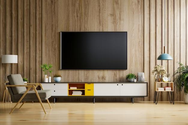 Tv auf schrank im modernen wohnzimmer mit lampe, tisch, blume und pflanze auf holzwandhintergrund.
