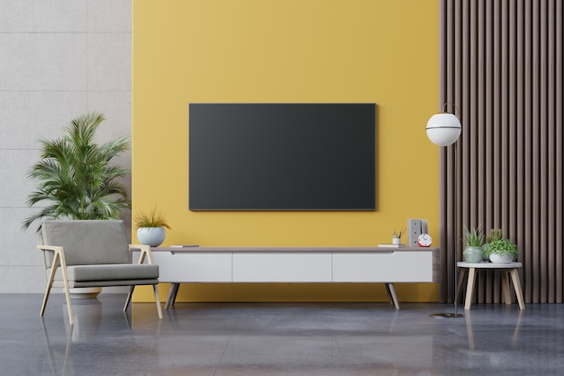Tv auf schrank im modernen wohnzimmer mit sessel, lampe, tisch, blume und pflanze auf gelber wand