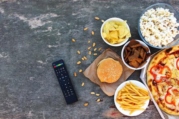 Tv-fernbedienung, fast food auf altem hölzernen hintergrund. konzept des junk-essens. draufsicht. flach liegen.
