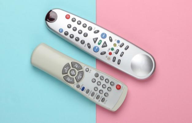 Tv-fernbedienungen auf einem blau-rosa pastell.