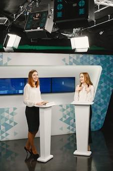 Tv-game-show mit zwei teilnehmern stehen auf tribünen. aufgeregte frauen im fernsehstudio, die fernsehsendungen filmen.