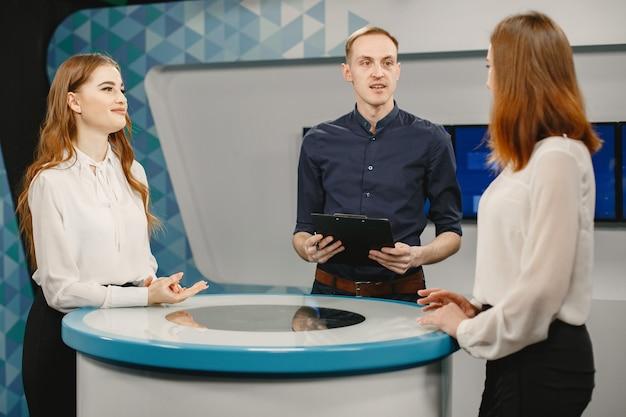 Tv-gameshow mit zwei teilnehmern, die fragen beantworten oder rätsel lösen und moderator. lächelnde frauen nehmen am fernsehquiz teil.