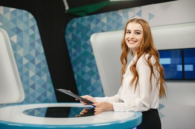 Tv-präsenz im studio, das sich auf die neue ausstrahlung vorbereitet. lächelndes mädchen im weißen hemd, das am tisch sitzt.
