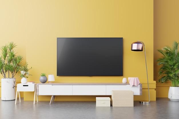 Tv-wandkonsole im modernen wohnzimmer mit lampe, tabelle, blume und pflanze auf gelbem beleuchtendem wandhintergrund, 3d-darstellung