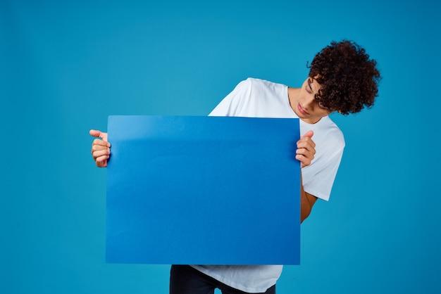 Typ, der ein blaues mockup-poster-exemplarstudio hält