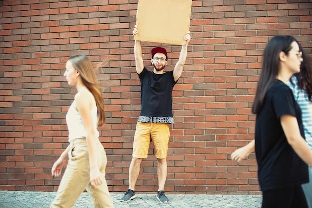 Typ mit schild - mann steht und protestiert gegen dinge, die ihn ärgern