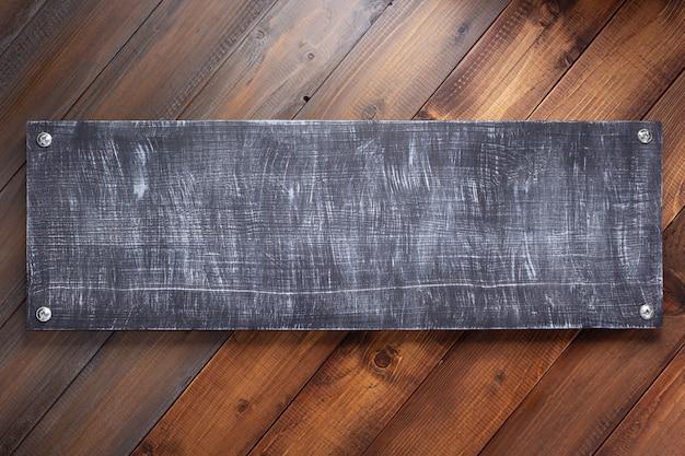 Typenschild oder wandschild an der hölzernen hintergrundtexturoberfläche mit schrauben