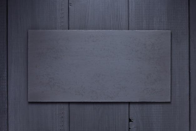 Typenschild oder wandschild an schwarzer holzhintergrundtexturoberfläche, mit schrauben