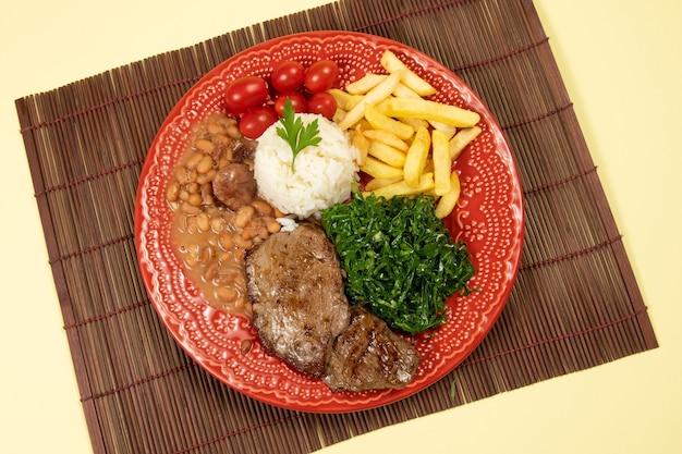 Typisch brasilianisches grundgericht mit reis, bohnen, steak, pommes frites, schmorkohl und tomate in einer roten schale