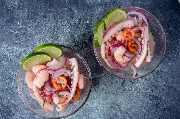 Typisch peruanisches essen, ceviche mit tintenfisch, garnelen und weißfisch mit lila zwiebeln und einer guten tigermilch.