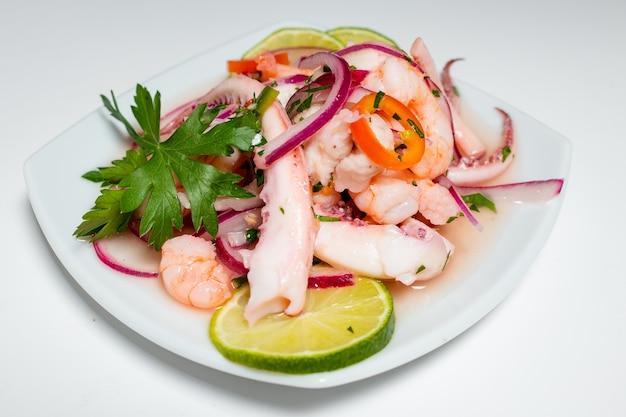 Typisch peruanisches essen, tintenfisch-ceviche, garnelen und weißer fisch mit lila zwiebeln und einer guten tigermilch.