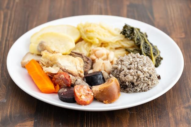 Typisch portugiesisches gericht gekochtes fleisch, geräucherte würste, gemüse und reis auf weißem teller