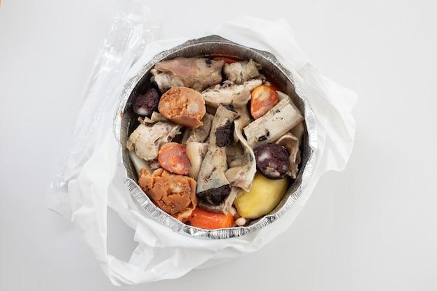 Typisch portugiesisches gericht gekochtes fleisch, geräucherte würste, gemüse und reis, zum mitnehmen