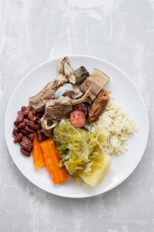 Typisch portugiesisches gericht gekochtes fleisch geräuchertes wurstgemüse und reis auf weißem teller