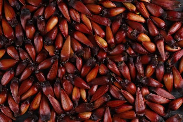 Typische araukariasamen, die im winter als gewürz in der brasilianischen küche verwendet werden. brasilianische ritzelmutter auf grauem holztisch. draufsicht.
