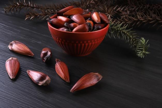 Typische araukariasamen, die im winter als gewürz in der brasilianischen küche verwendet werden. brasilianische ritzelnüsse in brauner und roter holzschale auf grauer holzoberfläche.