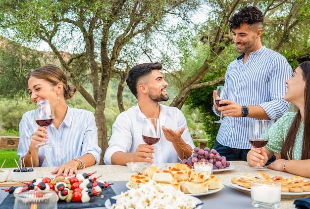 Typische italienische weinerntefeier im landhaus. gruppe junger freunde, die sich treffen