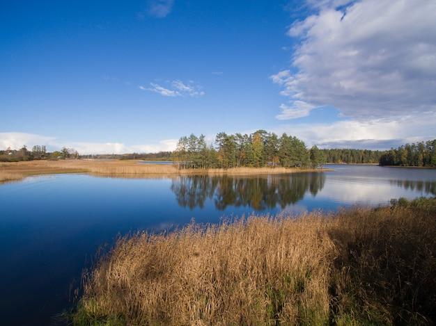 Typische landschaft in karelien - blauer himmel, wolken, großer see und viele entfernten grünen inseln, bäume, steine und felsen. russland, 2016