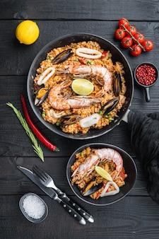 Typische spanische paella mit meeresfrüchten in traditioneller pfanne und schwarzer schüssel auf schwarzem holzhintergrund, flache lage, lebensmittelfoto.