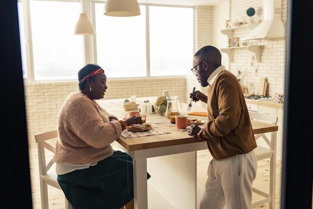Typischer morgen. nettes ehepaar, das beim frühstück in der küche ist