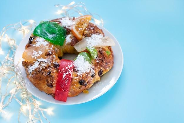 Typischer portugiesischer weihnachtsfruchtkuchen bolo rei auf blauem hintergrund