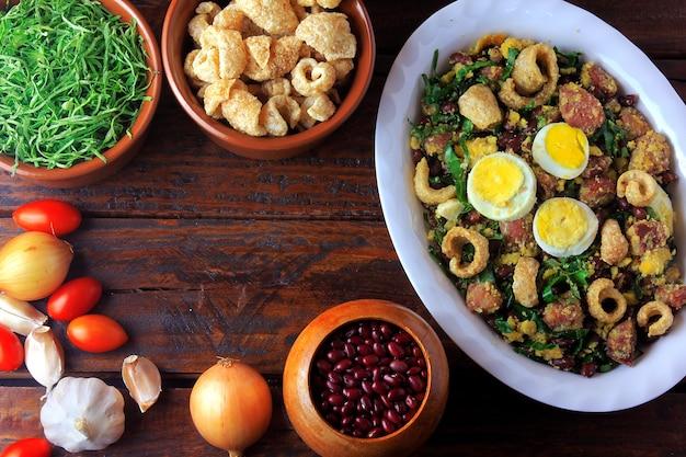 Typischer teller feijao tropeiro der brasilianischen küche, gemacht mit bohnen, speck, wurst, kohlgrüns, eier, auf rustikalem holztisch.