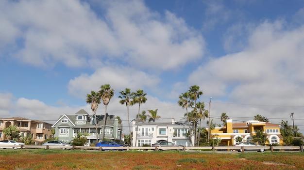Typischer vorort, tropisches carlsbad kalifornien usa. verschiedene bunte häuserreihe. generische amerikanische häuser, gebäudefassade, architektur außen. wohnviertel immobilien. himmel und palmen