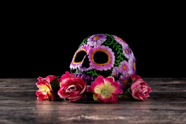 Typisches mexikanisches schädel- und blumendiadem auf schwarzem hintergrund. dia de los muertos.