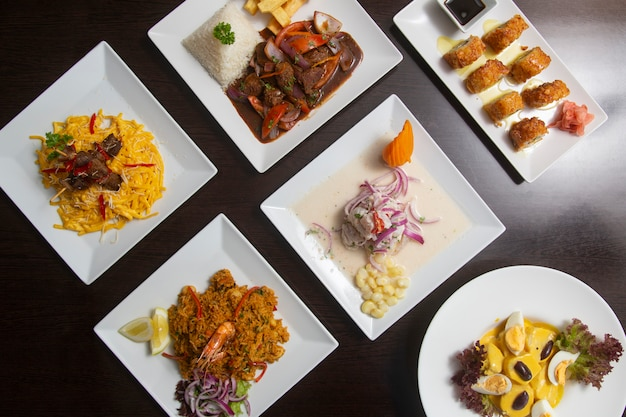 Typisches peruanisches essen von oben auf dunklem holztisch.