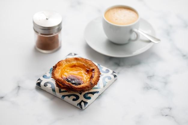 Typisches portugiesisches eierkuchen-pastell de nata mit einer tasse kaffee