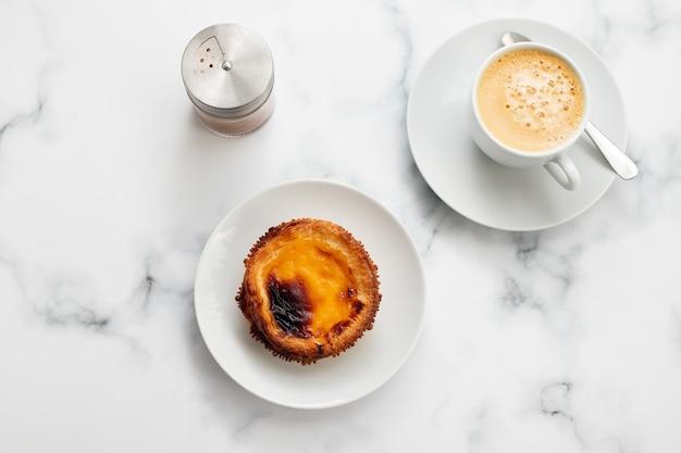 Typisches portugiesisches eierkuchenpastell de nata mit tasse kaffee auf keramikhintergrund