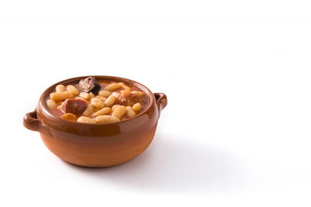Typisches spanisches fabada asturiana lokalisiert auf weißem oberflächenkopienraum