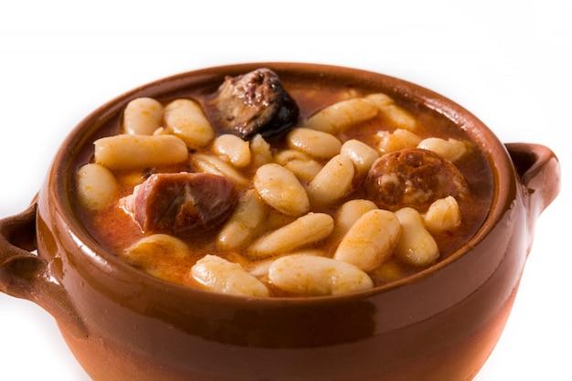 Typisches spanisches fabada asturiana lokalisiert auf weißer oberfläche.