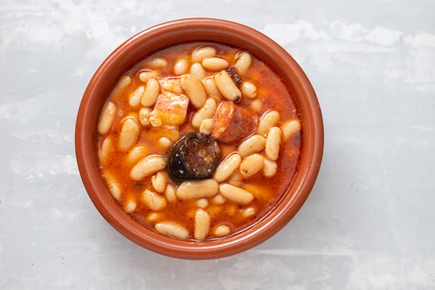 Typisches spanisches gericht fabada, bohnen mit geräucherten würstchen und fleisch auf brauner keramikschale
