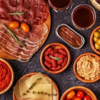 Typisches spanisches tapas-konzept. das konzept umfasst scheiben jamon, chorizo, wurst, schalen mit oliven, tomaten, sardellen, kichererbsenpüree, käse.
