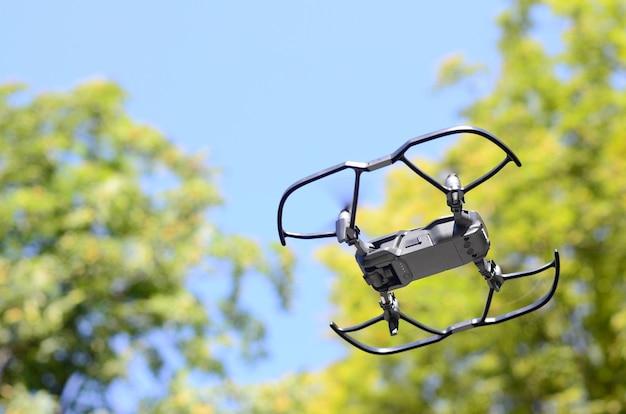 Uav-drohnencopter mit digitalkamera fliegt in der nähe der grünen bäume