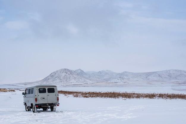 Uaz - russischer van im grasland mit schneebedeckten bergen auf hintergrund in mongolei