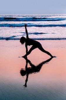 Übendes Yoga der jungen Frau auf Strand in Agonda, Goa, Indien