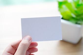 Übergeben Sie das Halten der leeren weißen Visitenkarte mit Kopienraum für Text, Geschäftsspott herauf backgrou