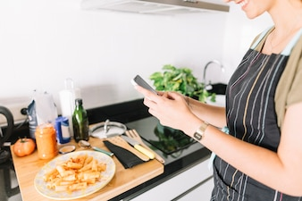 Übergibt die junge Frau, die Foto von köstlichen Teigwaren auf Smartphone macht