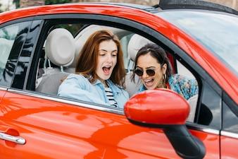 Überraschte junge Dame und fröhliche Frau, die im Auto sitzt