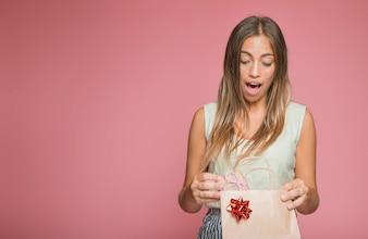 Überraschte junge Frau, die Geschenk von der Einkaufstasche gegen farbigen Hintergrund nimmt