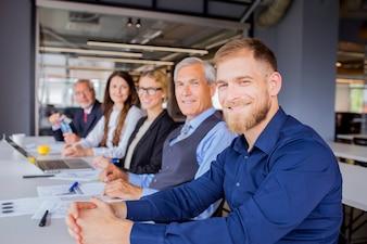 Überzeugte lächelnde Wirtschaftler, die zusammen im Geschäftstreffen sitzen