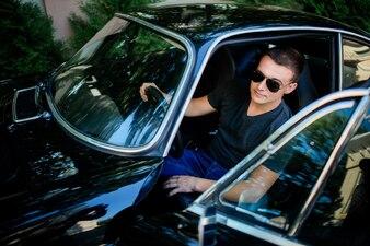 Überzeugter junger Mann in der Sonnenbrille sitzt innerhalb eines Retro- Autos des schwarzen Sports