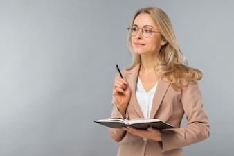 Überzeugter lächelnder blonder Behälter und Tagebuch der jungen Frau in der Hand gegen grauen Hintergrund