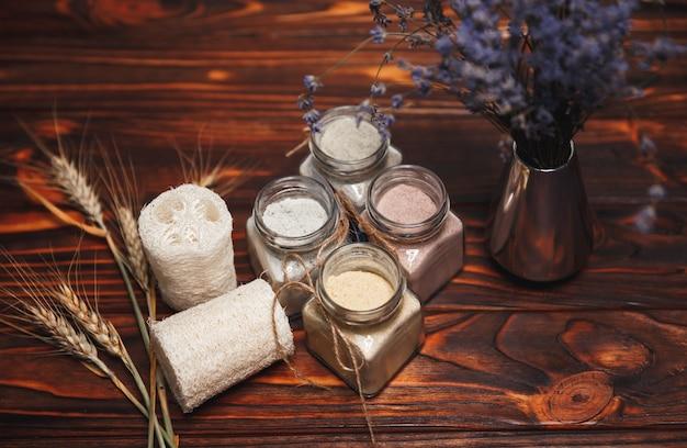 Ubtan ayurvedisch. kräuter-bio-ubtan in glasflasche mit getrockneten lavendelblüten auf hölzernem hintergrund