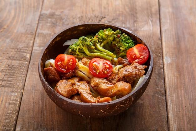 Udon mit fleisch und gemüse in yakiniku-sauce in einem teller mit kokosnussschalen auf einem holztisch. horizontales foto
